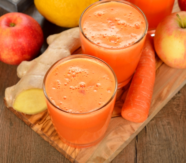 Fresh apple and carrot juice on brown background